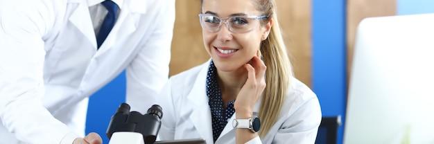 Junger mann und frau in weißen uniformen sitzen hinter tisch mit mikroskop