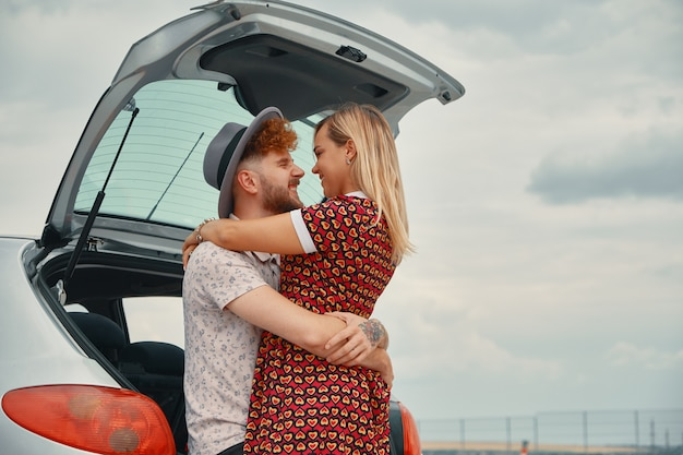 Junger mann und frau küssen im kofferraum