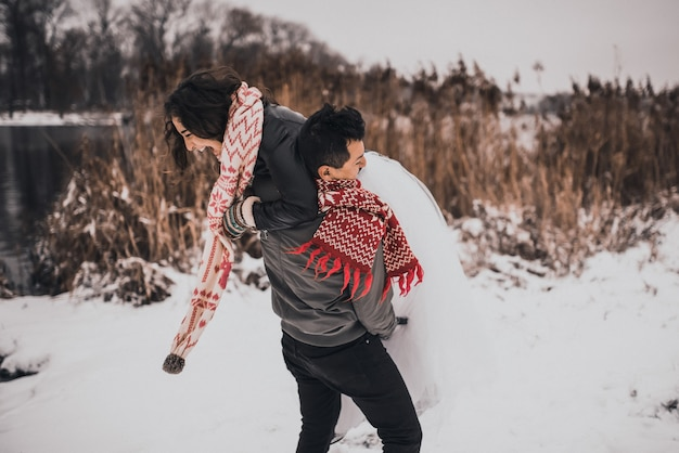 Junger mann und frau laufen im schnee liegend lachend herum und haben spaß daran, schneebälle zu spielen