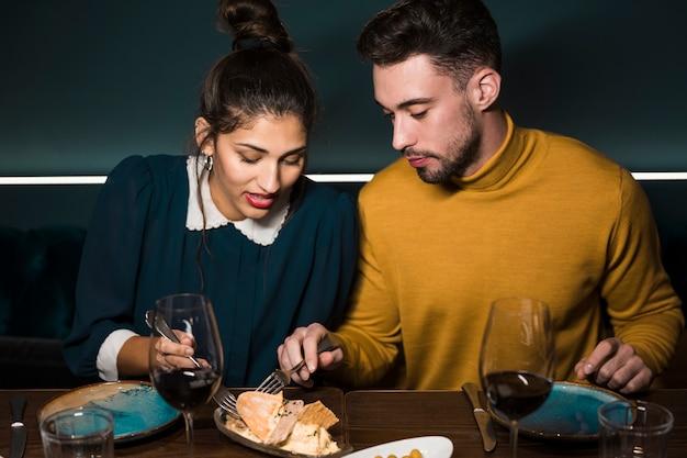 Junger mann und frau mit gabeln bei tisch mit gläsern wein und lebensmittel im restaurant