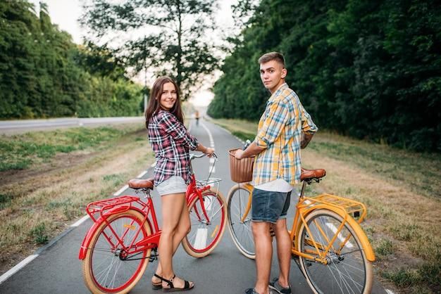 Junger mann und frau mit retro-fahrrädern. paar auf vintage-fahrrädern. alte zyklen, romantisches date