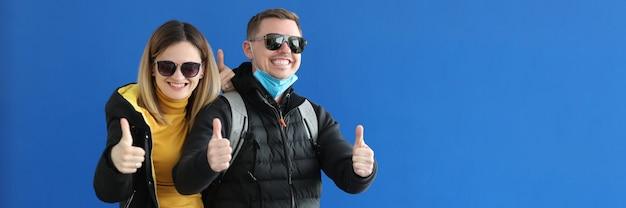 Junger mann und frau mit sonnenbrille und warmer kleidung, die daumen nach oben zeigen