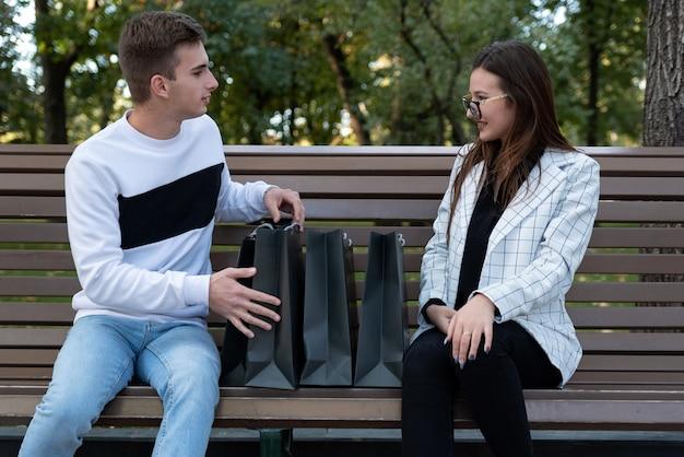 Junger mann und frau nach dem einkaufstag ruht auf der bank im park. paare mit einkaufstüten denken über das einkaufen nach.
