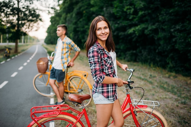Junger mann und frau posieren mit retro-fahrrädern. paar auf vintage-fahrrädern. alte zyklen, romantisches date