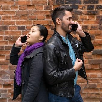 Junger mann und frau stehen rücken an rücken in der nähe einer mauer und telefonieren mit ihren handys
