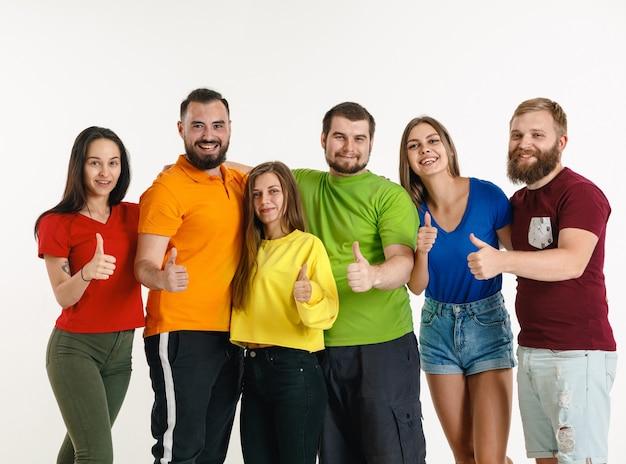 Junger mann und frau trugen in den farben der lgbt-flagge an der weißen wand. kaukasische modelle in hellen hemden. schauen sie glücklich, lächeln und umarmen. lgbt-stolz, menschenrechte und wahlkonzept.