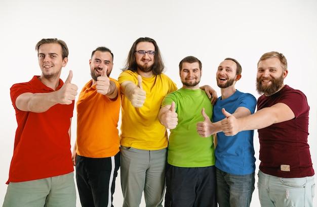 Junger mann und frau trugen in den farben der lgbt-flagge an der weißen wand. kaukasische modelle in hellen hemden. schauen sie glücklich zusammen, lächeln und umarmen. lgbt-stolz, menschenrechte und wahlkonzept.