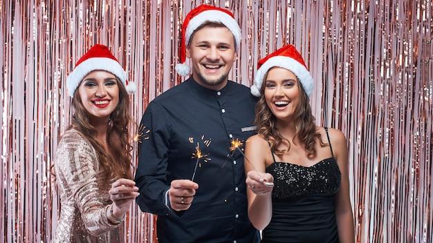 Junger mann und frauen, die weihnachten mit wunderkerzen in den händen genießt.
