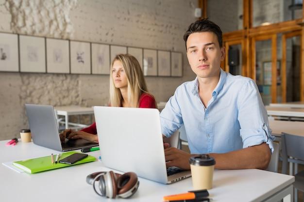 Junger mann und junge frau arbeiten am laptop im offenen raum zusammenarbeitenden büroraum,