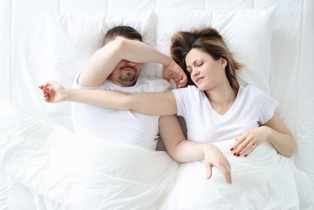Junger mann und junge frau, die im großen weißen bett schlafen