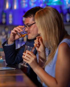 Junger mann und junge frau, die in der bar entspannen und getränke haben. nachtleben und abhängen