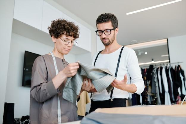 Junger mann und junge frau, die in der werkstatt stehen, während sie textil für neue modekollektion wählen