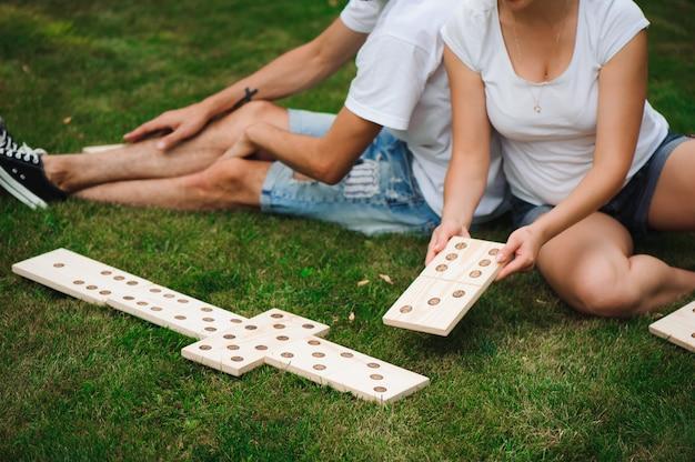 Junger mann und junge frau, die riesige dominosteine im park auf dem gras spielen