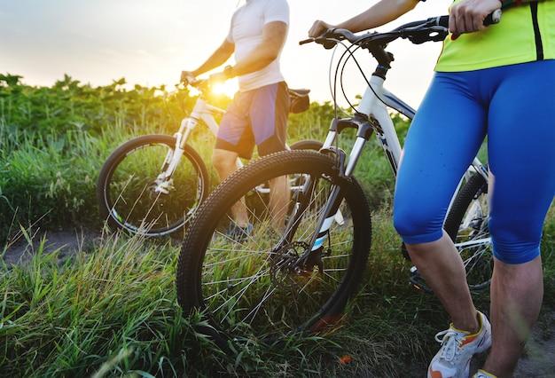 Junger mann und junge frau fahren im sommer mit dem fahrrad zum feld.