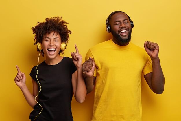 Junger mann und junge frau hören musik in kopfhörern