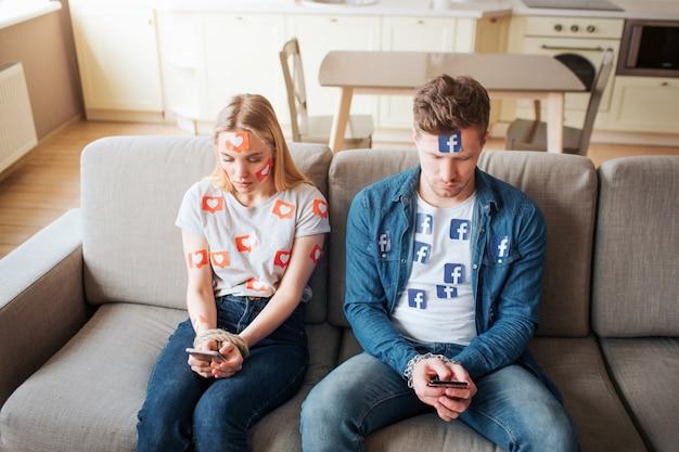 Junger mann und junge frau sind von sozialen medien abhängig. in telefonen stecken. auf dem sofa sitzen und schauen.