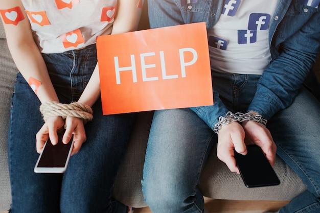. junger mann und junge frau sind von sozialen medien abhängig. schnittansicht von leuten, die auf sofa sitzen. telefon in händen. hilfepapier.