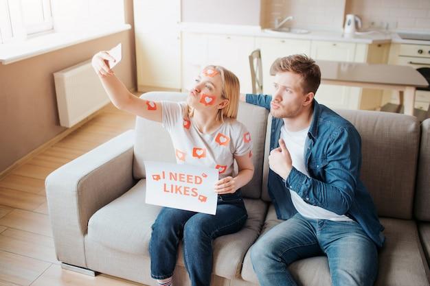 Junger mann und junge frau sind von sozialen medien abhängig. selfie mit dem telefon aufnehmen. posingo n kamera zusammen im raum auf dem sofa.