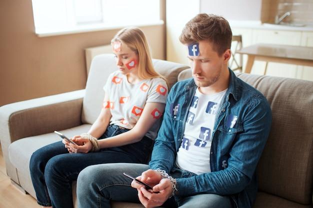 Junger mann und junge frau sind von sozialen medien abhängig. setzen sie sich auf das sofa im zimmer und schauen sie sich die telefone an. tageslicht.