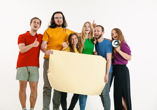 Junger mann und junge frau trugen in lgbt-flaggenfarben auf weißer wand. modelle in hellen hemden