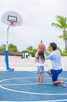 Junger mann und kleines mädchen, die draußen basketball am exotischen erholungsort spielt
