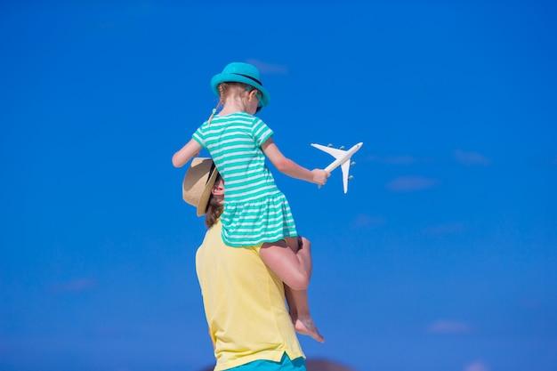 Junger mann und kleines mädchen mit miniatur des flugzeuges am strand