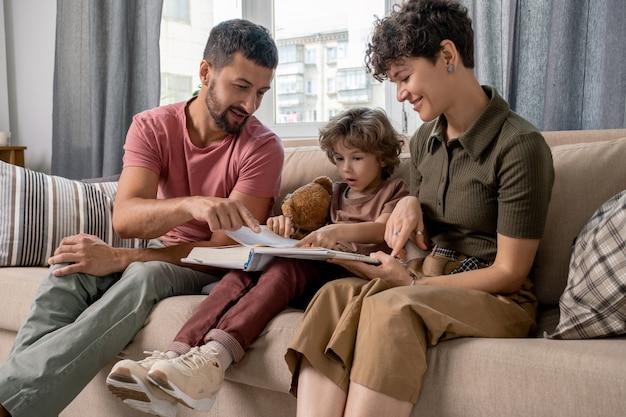 Junger mann und sein kleiner sohn zeigen auf seite der offenen enzyklopädie, während vater das thema des artikels oder der merkwürdigen tatsachen erklärt