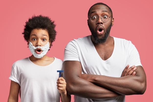 Junger mann und sein sohn mit dem lockigen haar, das rasiermesser hält