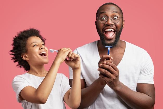 Junger mann und sein sohn mit dem lockigen haar, das rasiermesser und zahnbürste hält