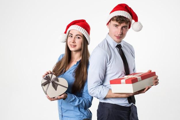 Junger mann und seine freundin in der weihnachtsmütze mit geschenken auf weißem hintergrund. weihnachtsfest.
