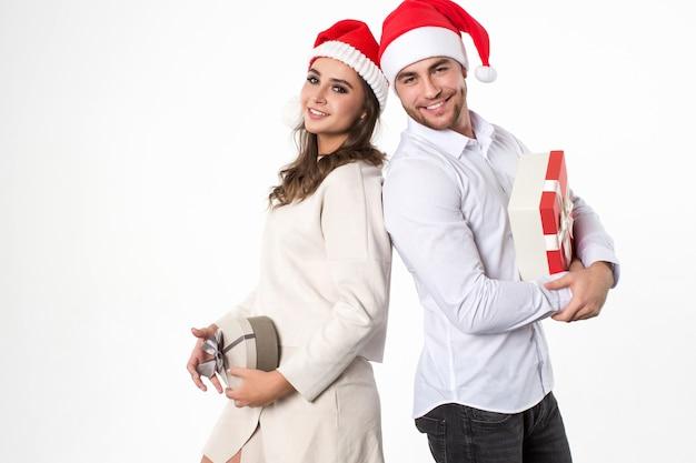 Junger mann und seine freundin mit geschenken auf weißem hintergrund. weihnachtsfest.