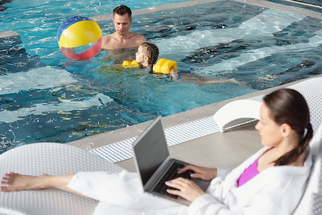 Junger mann und seine süße kleine tochter spielen mit ball im schwimmbad, während beschäftigte frau im bademantel mit laptop am pool im spa-center