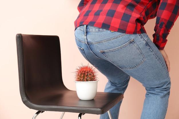 Junger mann und stuhl mit kaktus auf farbe. hämorrhoiden-konzept