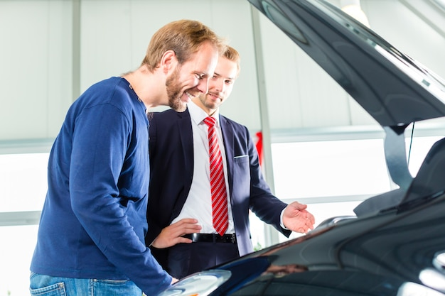 Junger mann und verkäufer mit auto im autohaus