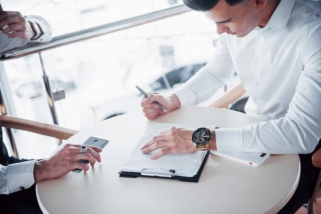 Junger mann unterschreibt dokumente im büro, erfolgreicher verkauf.