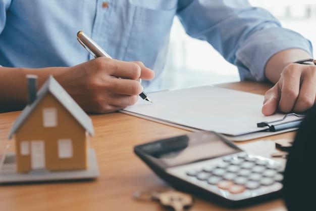 Junger mann unterschreibt finanzvertrag mit immobilienmakler im büro