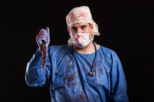 Junger mann verkleidet im arztkostüm für halloween auf schwarzem hintergrund. porträt des arztes mit bösem gesicht.