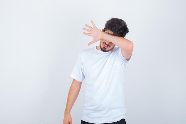 Junger mann versteckt augen hinter dem arm in weißem t-shirt und sieht verlegen aus