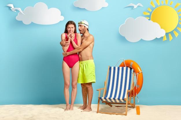 Junger mann versucht frau zu beruhigen, umarmt sie, trägt badehut, schutzbrille und grüne shorts