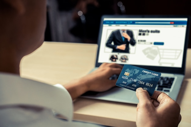 Junger mann verwenden kreditkarte für online-einkauf zahlung auf laptop-computer-anwendung oder website.