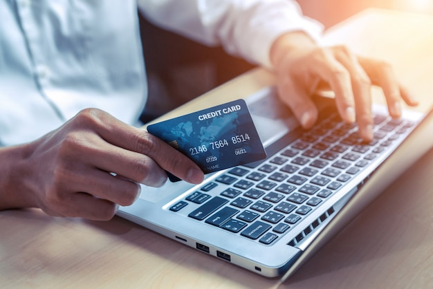 Junger mann verwenden kreditkarte für online-shopping