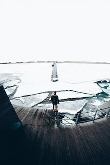 Junger mann vor einem gefrorenen meer in dänemark
