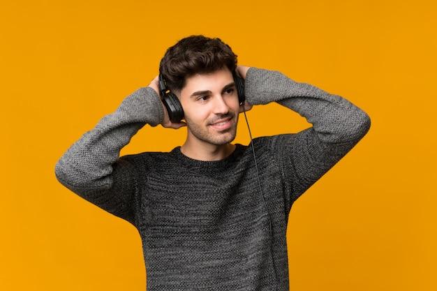 Junger mann vorbei lokalisiert unter verwendung des mobiles mit kopfhörern