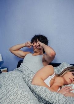 Junger mann wacht im bett auf, während seine frau schläft