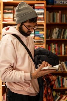 Junger mann wählt ein buch in einem geschäft aus.