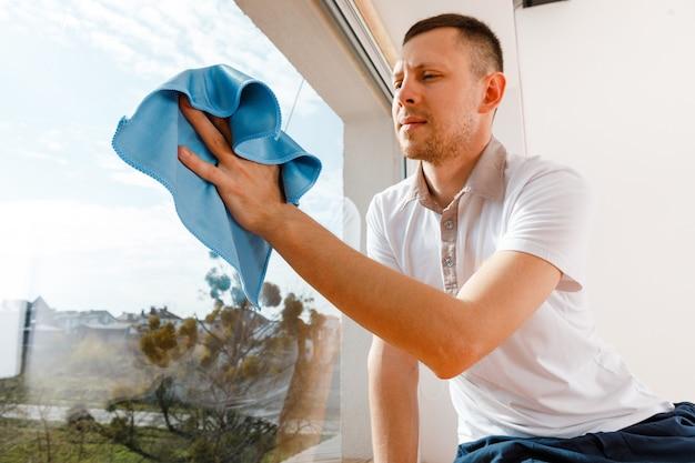 Junger mann wäscht fenster im büro