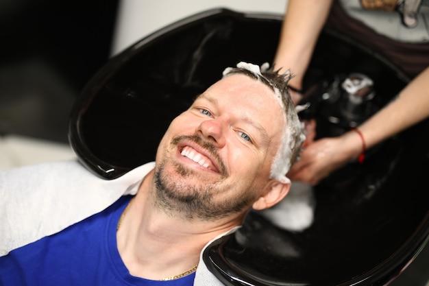 Junger mann wäscht haare mit shampoo im waschbecken im schönheitssalon