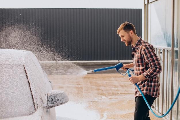 Junger mann wäscht sein auto in der waschanlage