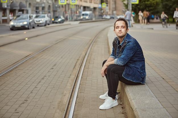 Junger mann wartet an einer straßenbahnhaltestelle auf die straßenbahn.