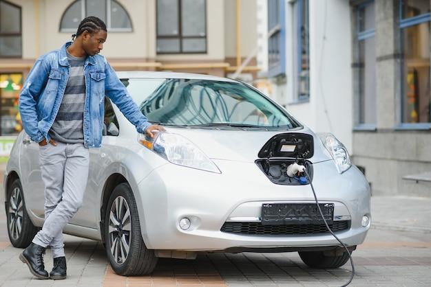 Junger mann wartet darauf, dass sein elektroauto aufgeladen wird